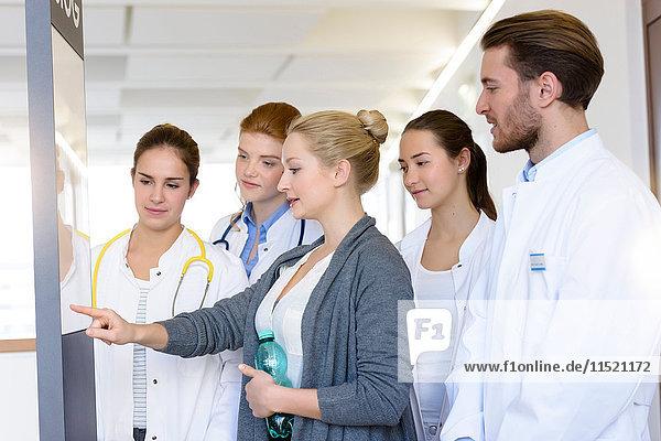Frau mit männlichen und weiblichen Ärzten  die im Krankenhaus auf das Krankenblatt zeigen