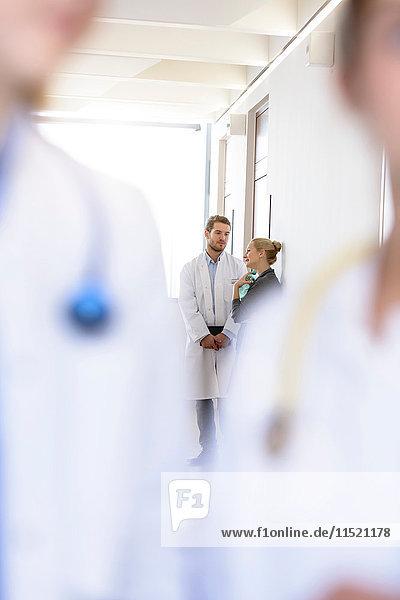 Über-Schulter-Ansicht eines männlichen Arztes und einer Frau bei einer Diskussion im Krankenhauskorridor