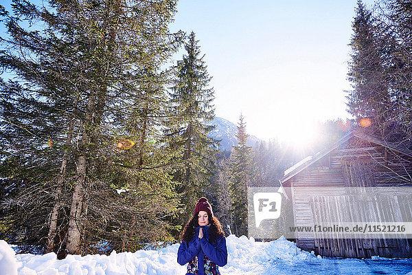 Frau praktiziert Yoga  meditiert im verschneiten Sonnenwald  Österreich