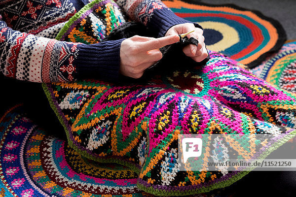 Mid section of woman sitting on floor crocheting  surrounded by crochet circles