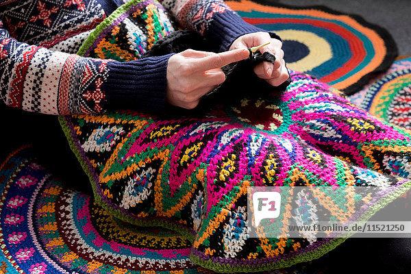 Mittlere Sektion einer Frau  die auf dem Boden sitzt und häkelt  umgeben von gehäkelten Kreisen