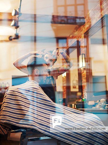 Blick durch das Fenster eines Friseurs  der den Kunden die Haare schneidet