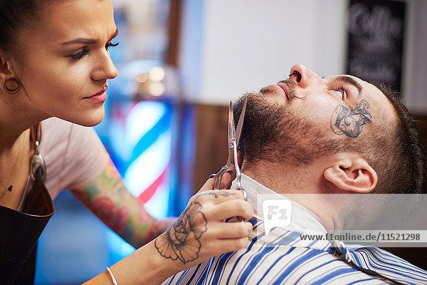 Friseur schneidet Kunden den Bart