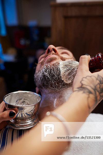 Frau trägt Rasierschaum auf den Bart des Mannes auf