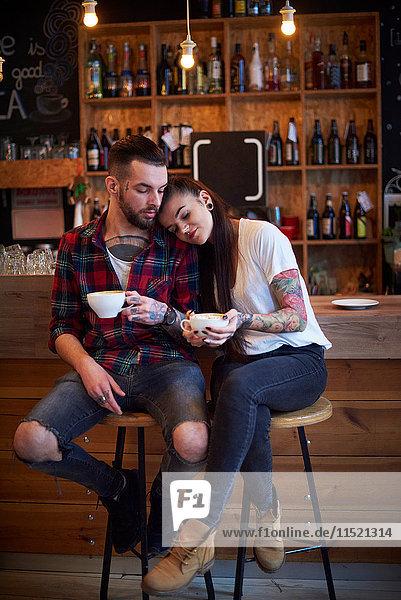 Paar sitzt nebeneinander auf Hockern im Cafe  Kopf auf der Schulter