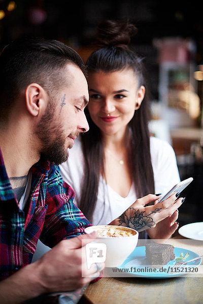 Paar mit Smartphone im Cafe