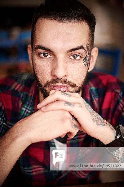 Portrait of tattooed man looking at camera