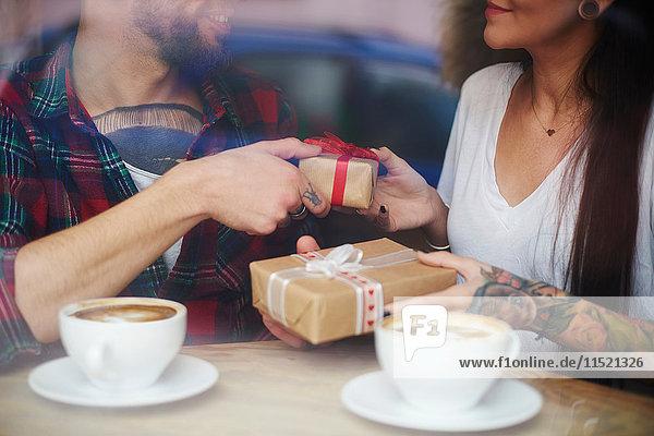 Blick durch das Fenster eines Paares in einem Café  das Geschenke austauscht