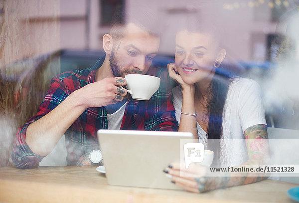 Blick durch das Fenster eines Paares im Café mit einem digitalen Tablett