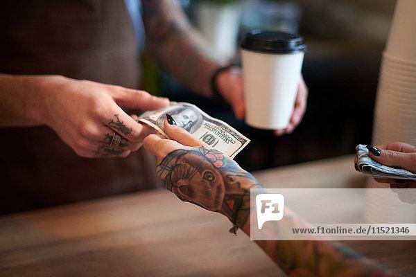 Kundin  die ihren Kaffee mit Bargeld bezahlt