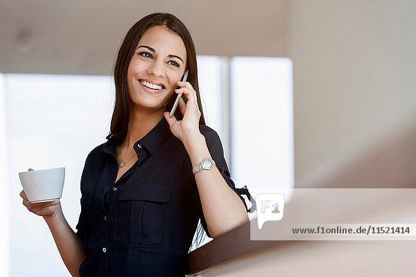 Junge Geschäftsfrau mit Kaffeetasse im Bürokorridor beim Telefonieren mit dem Smartphone