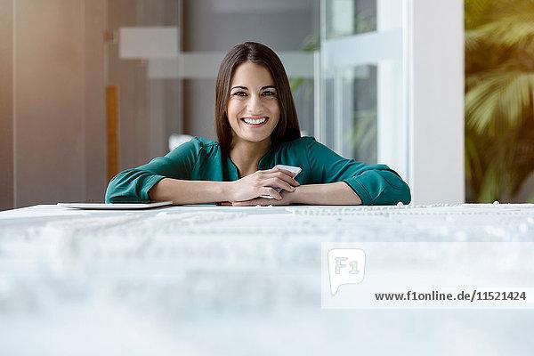 Porträt einer jungen Geschäftsfrau im Büroempfang mit Smartphone und digitalem Tablet
