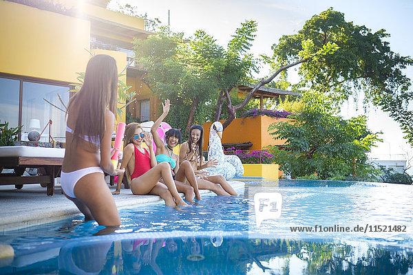 Vier junge Frauen mit Spaß am Pool