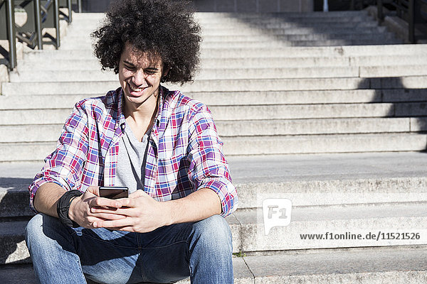 Portrait of smiling young man sitting on stairs looking at cell phone