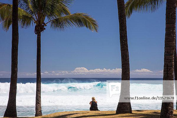 Touristin sitzt am Strand mit Blick auf den Indischen Ozean  Insel Réunion