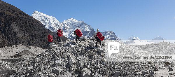 Nepal  Himalaya  Khumbu  Everest-Region  Träger am Ngozumpa-Gletscher