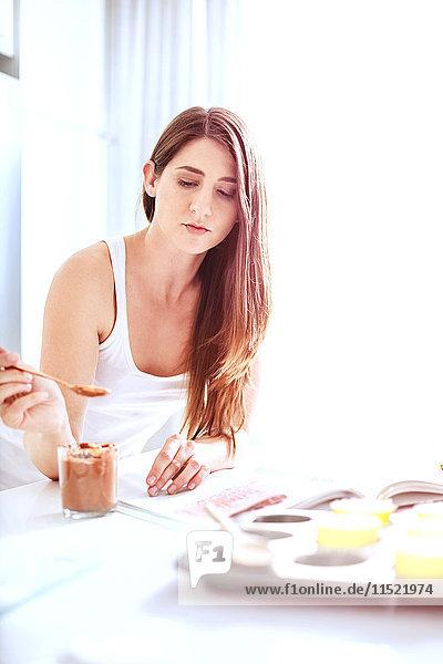 Frau isst mit Löffel Toffee aus der Dose