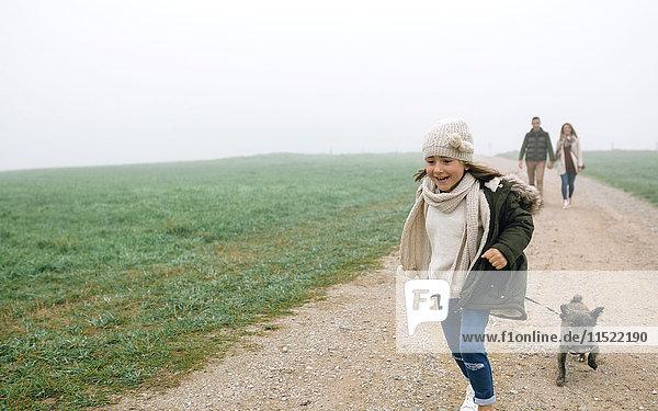 Glückliches Mädchen läuft mit ihrem Hund  während ihre Eltern an einem nebligen Wintertag im Hintergrund spazieren gehen. Glückliches Mädchen läuft mit ihrem Hund, während ihre Eltern an einem nebligen Wintertag im Hintergrund spazieren gehen.