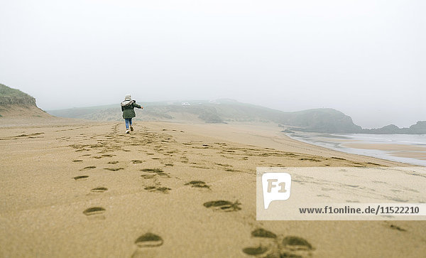Girl running on the beach on a foggy winter day