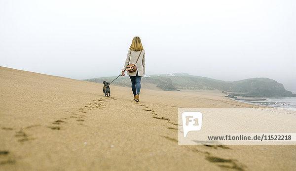 Frau beim Spaziergang mit Hund am Strand im Winter Frau beim Spaziergang mit Hund am Strand im Winter