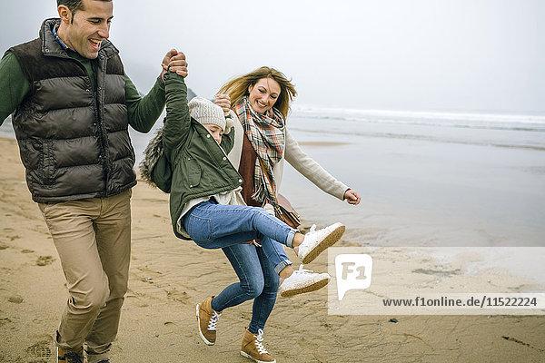 Glückliche Eltern  die ihre Tochter im Winter am Strand aufziehen.