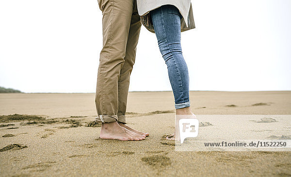Niedriger Abschnitt des Paares  das barfuß am Strand steht.