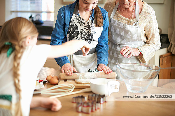 Senior woman and granddaughters rolling dough for Christmas tree cookies