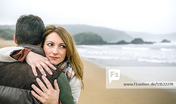 Frau umarmt Mann am Strand im Winter