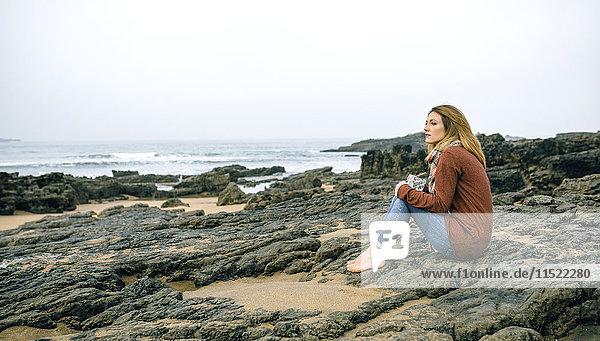 Einsame Frau sitzt im Winter auf Felsen am Strand.