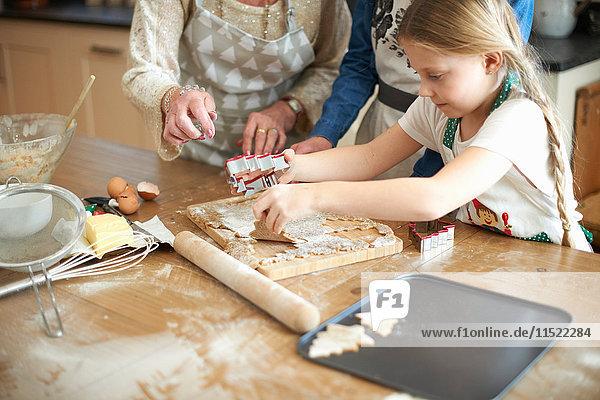 Schnappschuss einer älteren Frau und Enkelinnen beim Schneiden von Weihnachtsbaumplätzchen an der Küchentheke