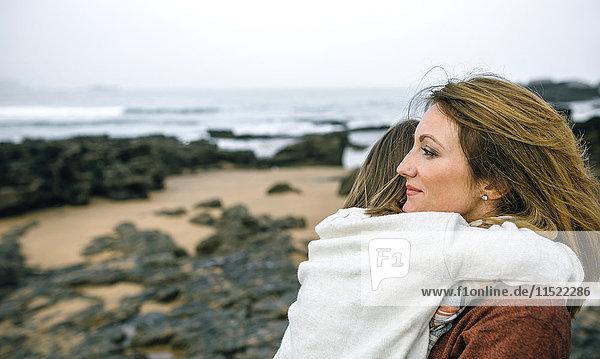 Mutter mit Tochter am Strand im Winter