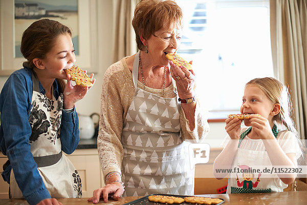 Senior woman and granddaughters eating freshly baked Christmas tree cookies