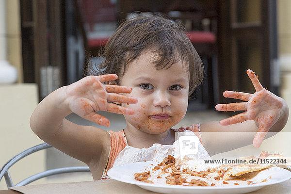 Porträt eines kleinen Mädchens  das Spaghetti mit Fingern isst.