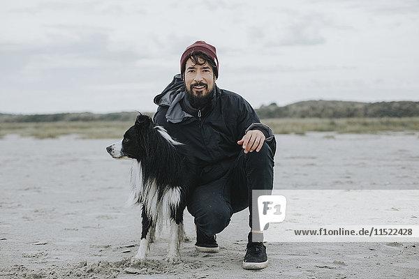 Niederlande  Schiermonnikoog  Mann mit Border Collie am Strand