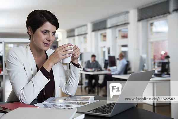 Frau mit Laptop im Büro mit Kollegen im Hintergrund