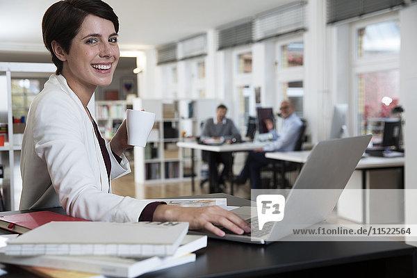 Porträt einer glücklichen Frau mit Laptop im Büro mit Kollegen im Hintergrund