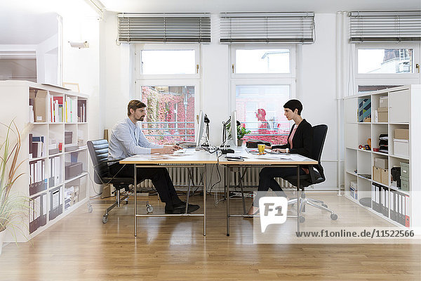 Kollegen am Schreibtisch im Büro