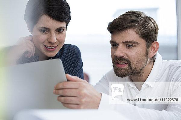 Kollegen im Büro teilen sich Tablett