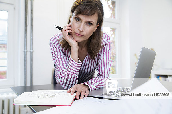 Woman with laptop in office thinking