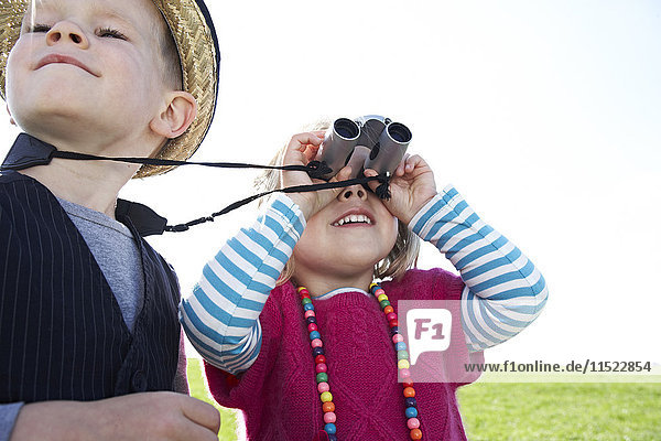 Boy and girl with binoculars on meadow