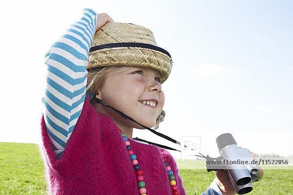 Girl with binoculars on meadow