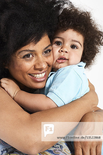 Portrait of little boy cuddling with his mother