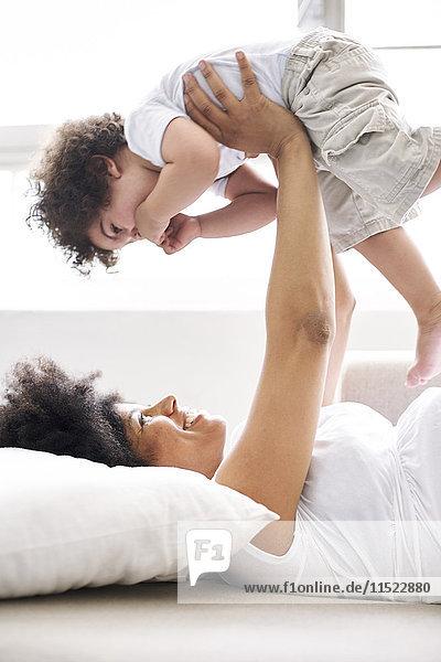 Schwangere Frau spielt mit ihrem kleinen Sohn zu Hause