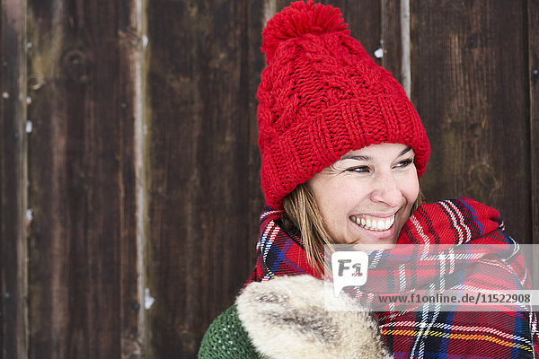 Portrait of smiling woman wearing red bobble hat in winter