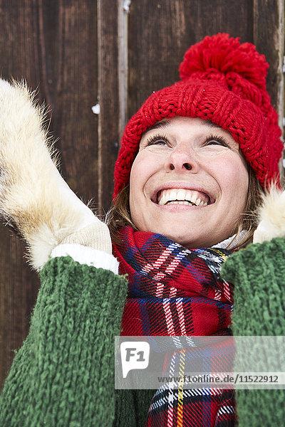 Porträt einer lächelnden Frau mit rotem Pudelhut im Winter
