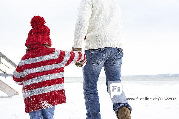 Vater und Tochter gehen im Schnee  Rückansicht