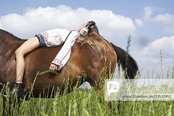 Girl with headphones lying on horseback