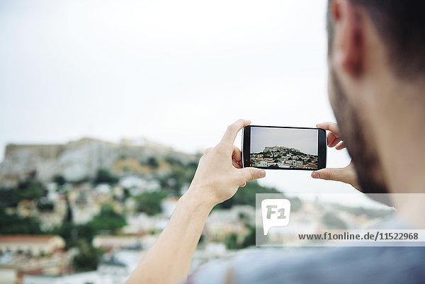 Griechenland  Athen  Mann beim Fotografieren des Parthenon-Tempels in der Akropolis  umgeben von der Stadt.