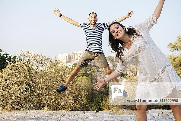 Griechenland  Athen  glückliches Paar beim Springen auf Areopagus mit der Akropolis und Parthenon im Hintergrund