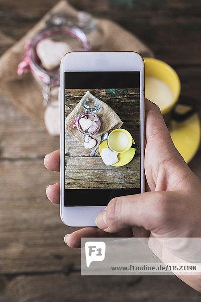 Frau beim Fotografieren von Mürbegebäck und Tasse Milch mit ihrem Smartphone  Nahaufnahme